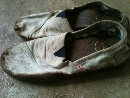 sepatu yang babak belur karena lumpur.